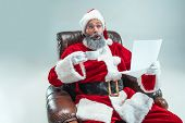 Funny Serious Guy With Christmas Hat Sitting At Studio With A Letter Of Desire. New Year Holiday. Ch poster
