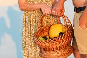 Couple Holding A Wicker Basket With Fruit, Man And Woman Having A Picnic On The White Sand Beach Or  poster