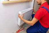 Plumbing Services - Plumber Installing Heating Radiator On The Wall poster