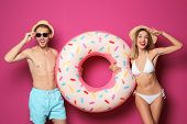 Happy Young Couple In Beachwear With Inflatable Ring On Color Background poster