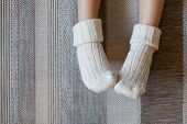 Legs Of Little Child Girl Is In Woolen Knitted Socks. Kid Is Sitting On Warm Floor With Carpet And H poster