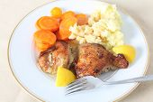 stock photo of thigh highs  - A high angle view of chicken thighs marinaded in lemon juice and herbs and then roasted served with mashed boiled potatoes and boiled carrots - JPG