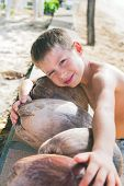 Caucasian Boy Has Collected Coconuts On Beach Natural Product Food Of Thailand Brown Coconut Or Coco poster