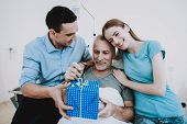 Gift For Old Man In Clinic. Young Family Give Old Man Gift. Happy Family. Good Mood In Family. Famil poster