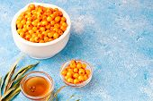 Sea-buckthorn Berries In Bowl And Natural Honey Or Sea Buckthorn Oil On Blue Background poster