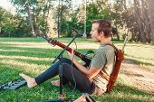 Portrait Of White Caucasian Male Musician Playing Guitar In Park Outside On Summer Sunset. Man Perfo poster