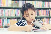 Asian Girl In Library Reading Something In A Book And Choosing A Book In A Library.  Education  And  poster