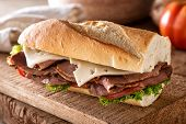 A Delicious Roast Beef Sandwich With Swiss Cheese, Lettuce And Tomato On A French Bread Baguette. poster