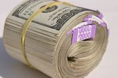 picture of ten thousand dollars  - Ten Thousand Dollars American Cash rolled up and held together with yellow rubber band - JPG