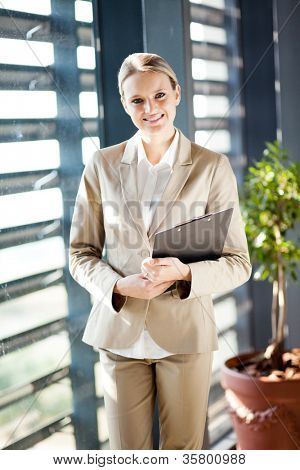 pretty young businesswoman standing by office window