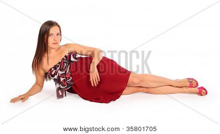 Beautiful young woman dressed in red pareo lies in studio on white background.