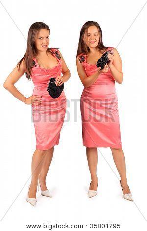 zwei gleiche Frauen tragen Rosa Abendkleid im Studio auf weißen Hintergrund. erste Frau schaut in die Kamera