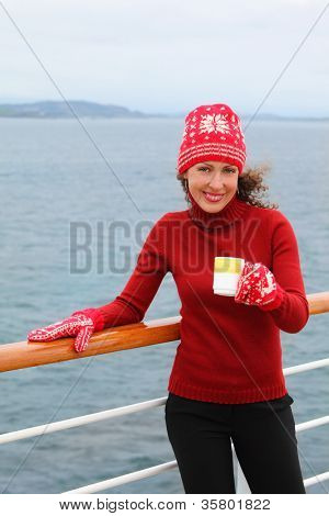 Smiling woman wearing in red hat and mittens holds cup of hot tea at ship deck
