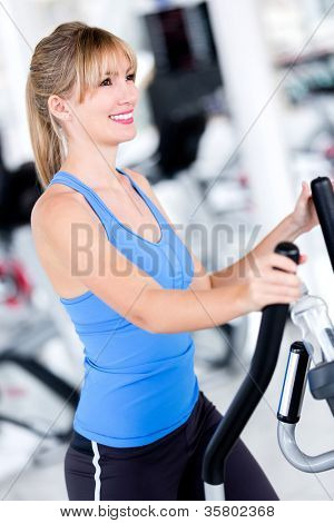Fit woman at the gym exercising looking happy