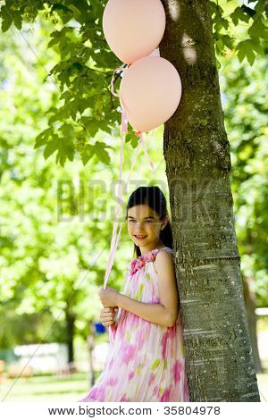 Cute little girl with pink ballloons, standing outdoors