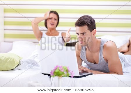 Problems in bed, woman screaming at man while he works on laptop