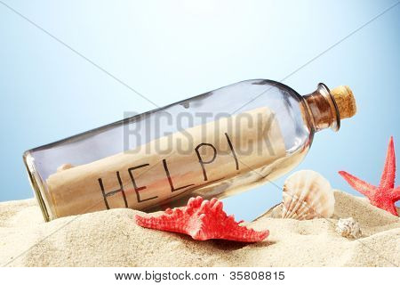 Glass bottle with note inside on sand, on blue background