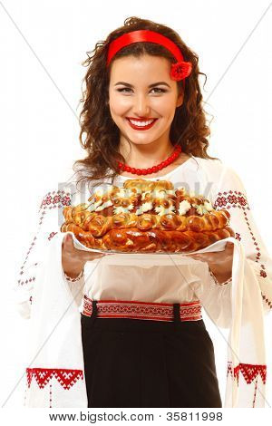 Beautiful ukrainian young hospitable woman in native costume by tradition holding embroidered towel and round loaf, on white background