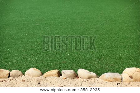 Background with artificial grass. In the foreground is sand with stones.
