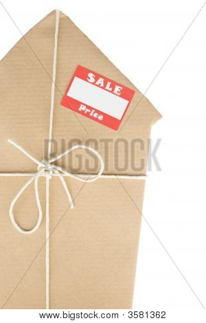 House Wrapped In Brown Paper With Sale Sticker