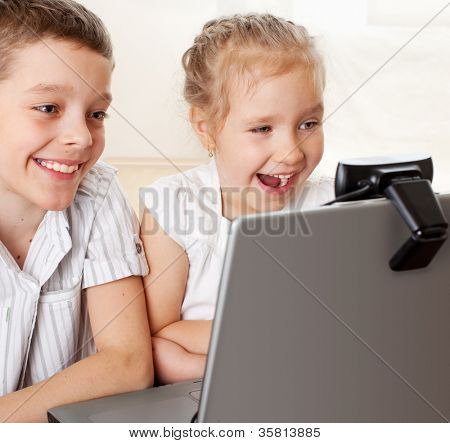 Ã?Â??hildren communicate with online. Happy kids with laptop at home