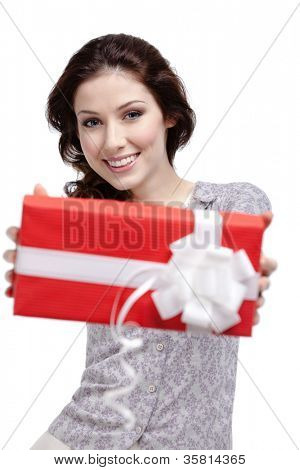 Young woman passes a gift wrapped in red paper, isolated on white
