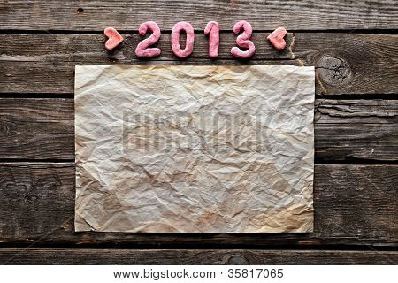 Old crumpled paper with dried / craft flowers and numbers 2013 on old wood. Sweet New Year holiday background.