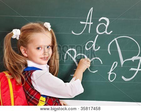 Schoolchild writting on blackboard in schoolroom.