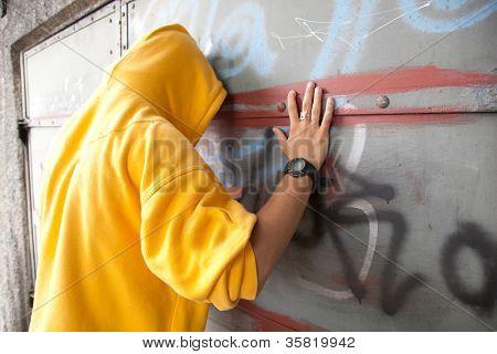 Young man in hooded sweatshirt / jumper facing grunge graffiti wall. Conceptual
