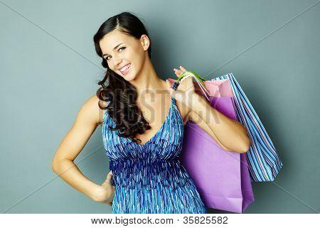 Retrato de morena feliz com paperbags olhando para câmera com sorriso