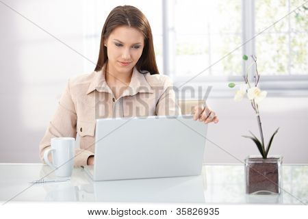 Youn businesswoman working at home, using laptop, smiling.