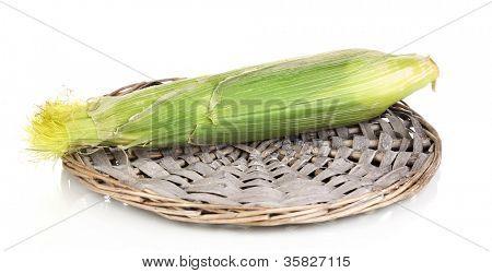 Fresh corn cob on wicker mat isolated on white