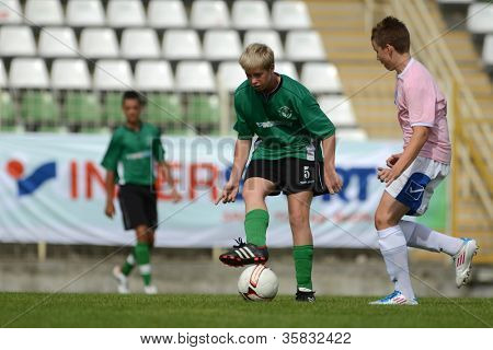 KAPOSVAR, HUNGARY - JULY 21: Unidentified players in action at the VIII. Youth Football Festival U14 match Tirgu Mures (pink) (ROM) vs. Kaposvar (green)(HUN) on July 21, 2012 in Kaposvar, Hungary
