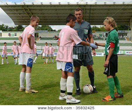 KAPOSVAR, HUNGARY - JULY 21: Team captains shake hands at the VIII. Youth Football Festival U14 match Tirgu Mures (pink) (ROM) vs. Kaposvar (green)(HUN) on July 21, 2012 in Kaposvar, Hungary