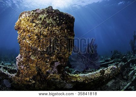 Coral encrusted shipwreck with sunburst through blue water