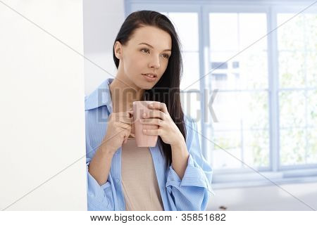 Early morning portrait of beautiful young woman drinking tea.