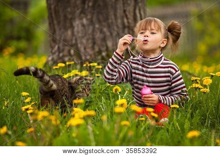 Portrait of funny lovely little girl and a cat, blowing soap bubbles.