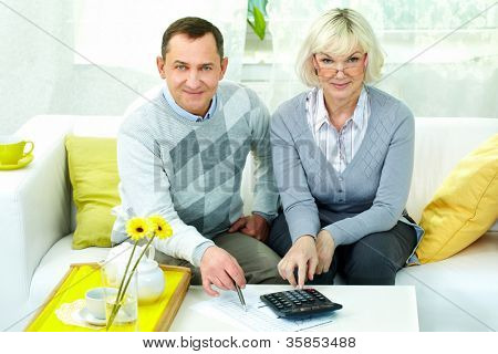 Portrait of mature man and his wife looking at camera while making financial revision at home