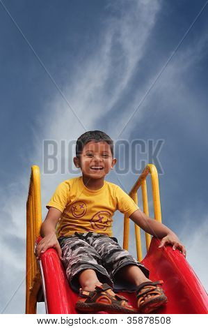 Happy Smiling And Handsome Indian Kid Having Fun Playing In Slider At A Park On A Bright Sunny Day.