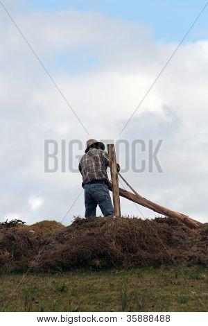Farmer Building a Fence