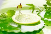 image of miniature golf  - Miniature Figures playing golf on fruits - JPG