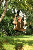 picture of swingset  - Girl sit on a swing and swinging outside in a garden - JPG