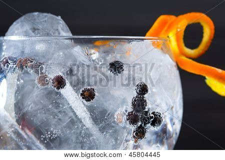 Gin tonic cocktail macro closeup with juniper berries orange