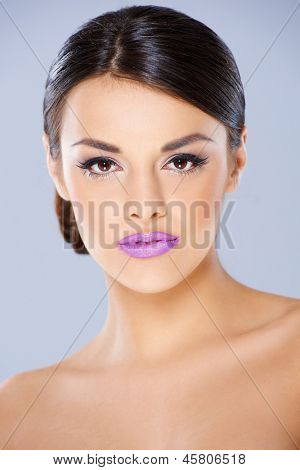 Beautiful girl with violet lips looking stright into camera