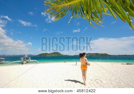 one bikini girl holds coconut on white beach