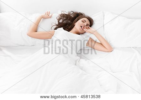young woman sleeping on the white linen in bed