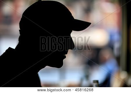 Silhouette of man in baseball cap indoors over bokeh blur background. Closeup, copyspace.