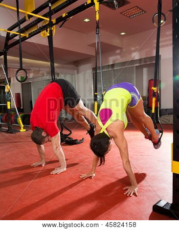 Crossfit fitness TRX training exercises at gym woman and man push-up pushup