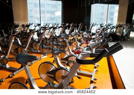 Aerobics exercise bikes gym room with many in a row