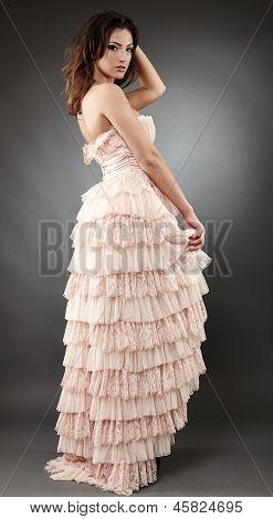 Beautiful Woman Wearing Ruffled Dress On Gray Background